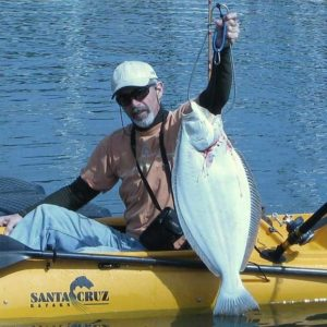 man on a santa cruz kayak catching a fish