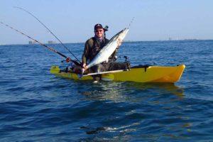 man with a caught fish on a santa cruz kayak